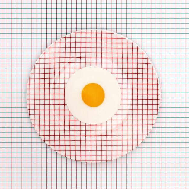 Plate of a fried egg on a table with a geometric pattern Free Photo