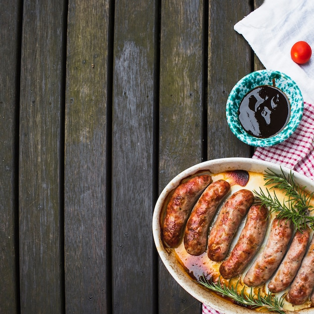 Plate of grilled sausages served with sauce Free Photo