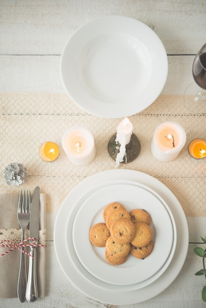 Plate of homemade biscuits on table set up for christmas dinner Free Photo