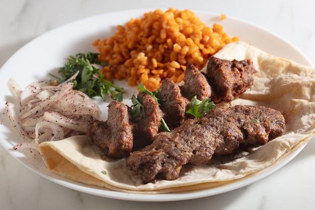 Piatto di kebab con pane e cipolle e riso speziato Foto Gratuite