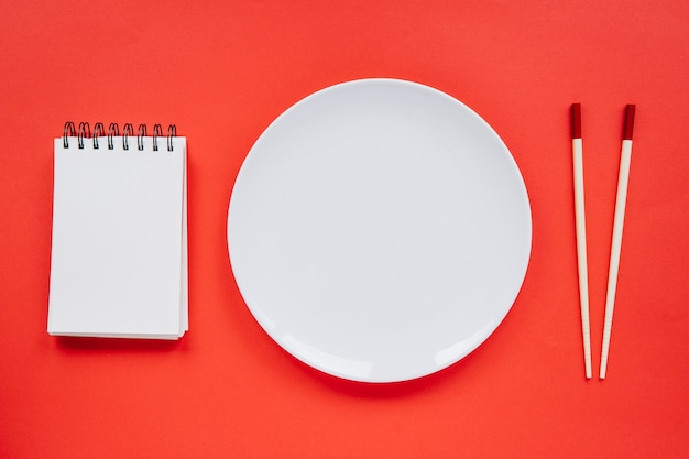 Plate between notebook and chopsticks Free Photo