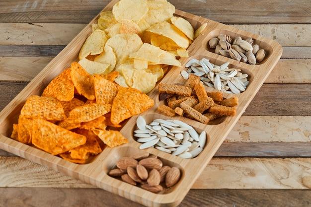 木製のテーブルに盛り合わせスナックのプレート。チップス、クラッカー、アーモンド、ピスタチオ、ヒマワリの種。 無料写真