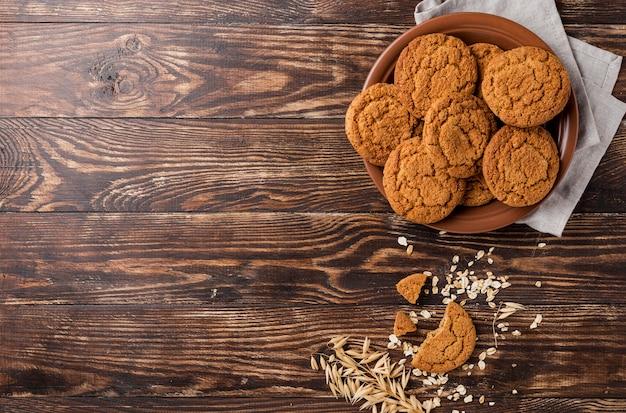 Тарелка вкусных печенья и деревянная копия космический фон Premium Фотографии