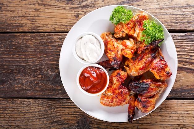 나무 테이블, 평면도에 튀긴 된 닭 날개의 접시 프리미엄 사진