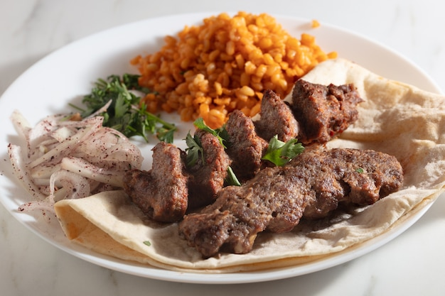 빵과 양파, 매운 밥을 곁들인 케밥 접시 무료 사진