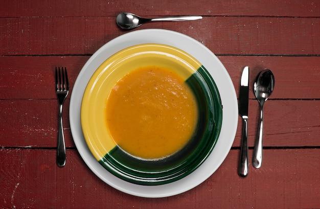 赤い木製のテーブルの上のカボチャスープのプレート Premium写真