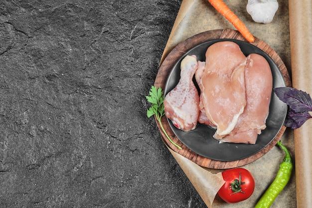 어두운 표면에 토마토와 당근 원시 치킨 부품 접시 무료 사진