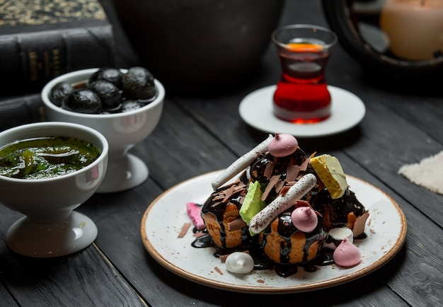 A plate of profiteroles served with chocolate sauce Free Photo