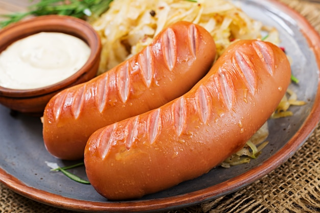Plate of sausages and sauerkraut on wooden table. traditional oktoberfest menu Free Photo