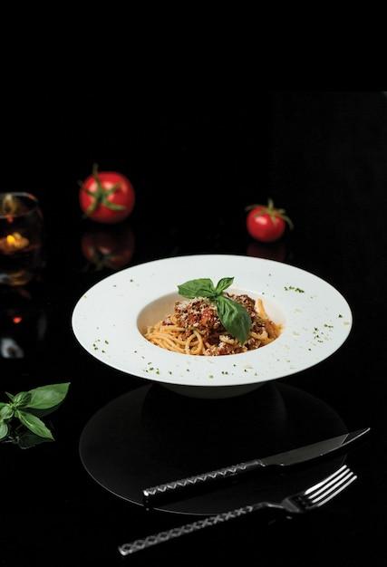 A plate of spaghetti in dark restaurant. Free Photo