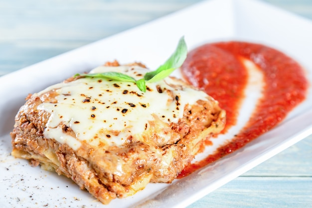 Plate of traditional meat lasagna with tomato sause Premium Photo