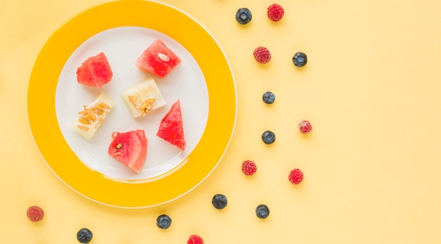 Plate of watermelon and muskmelon slices on plate with blueberries and raspberries on yellow background Free Photo