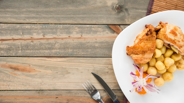 Plate with chicken breast and gnocchi on wooden table Free Photo