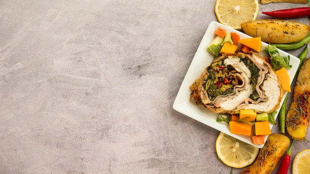 Plate with chicken roll and vegetables on concrete table Free Photo