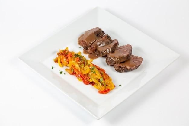 Тарелка с вареной говядиной с нарезанным разноцветным перцем, залитая соусом Бесплатные Фотографии