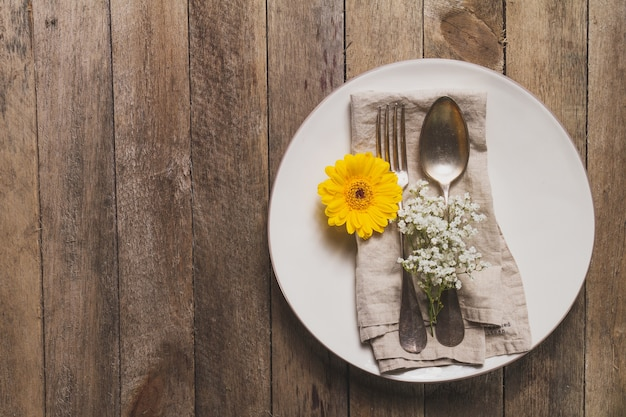 Plate with cutlery and flower on wooden table Free Photo