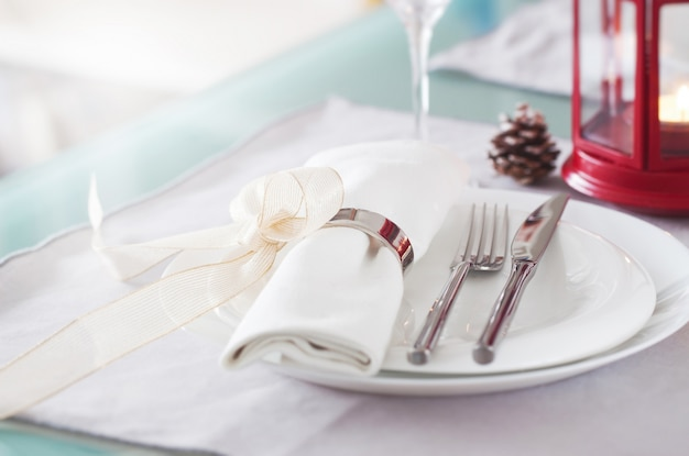 Plate with cutlery well decorated with napkin tied with a golden bow Free Photo