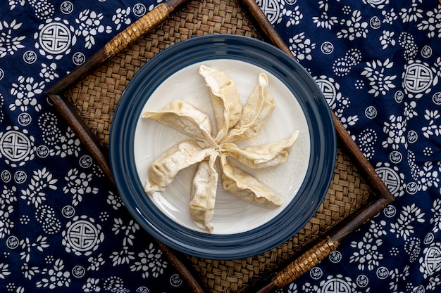 Plate with dim sum on a wooden stand on a blue and white floral background Premium Photo