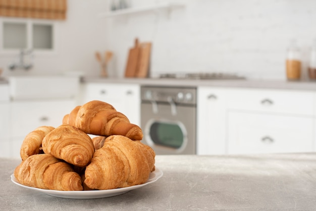 Plate with fresh croissants on table Free Photo