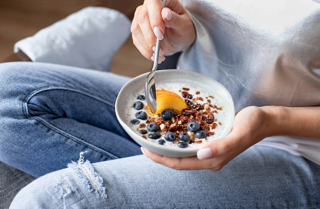 Plate with granola and fresh berries in the hands of a young girl Premium Photo