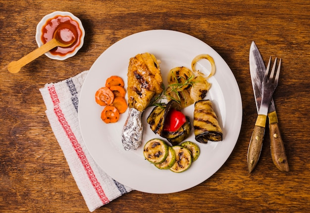 Plate with grilled chicken leg and vegetables Free Photo