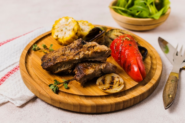 Plate with grilled vegetables and meat on table Free Photo