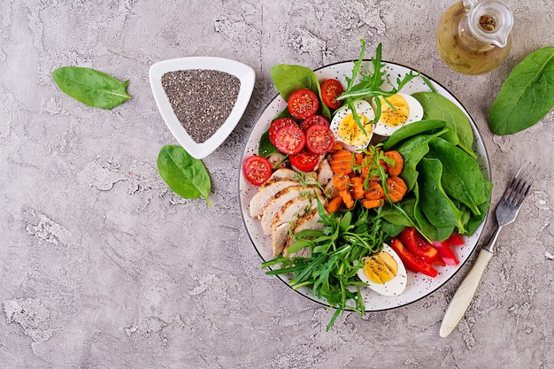 Plate with a keto diet food. cherry tomatoes, chicken breast, eggs, carrot, salad with arugula  and spinach. keto lunch. top view Premium Photo