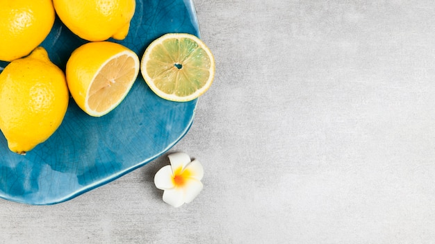 Plate with lemon on wooden background with copy space Free Photo
