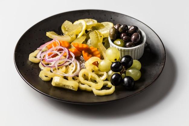 漬物、コショウ、玉ねぎ、にんじんのマリネと白と黒のブドウとオリーブのプレート 無料写真