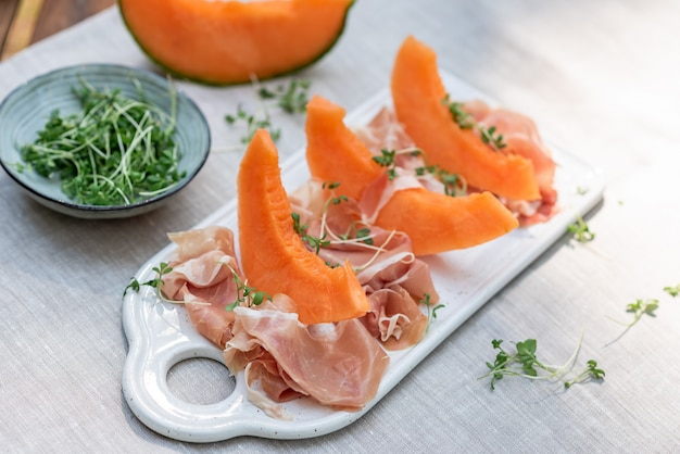 Plate with melon and jamon, wooden table, snack Premium Photo
