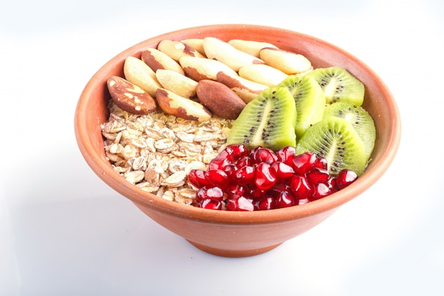 A plate with muesli, kiwi, pomegranate, brazil nuts isolated on white background. Premium Photo