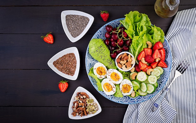 Plate with a paleo diet food. boiled eggs, avocado, cucumber, nuts, cherry and strawberries. paleo breakfast. top view Free Photo