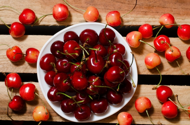 Plate with red cherries on wooden plates, yellow and red cherry, top view Premium Photo