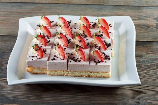 Piastra con cheesecake a fette decorata con crosta di cioccolato e fragole poste sul tavolo in legno ristorante cafe coffee shop panetteria cottura cucina pasticceria dolce concetto di dessert. Foto Gratuite