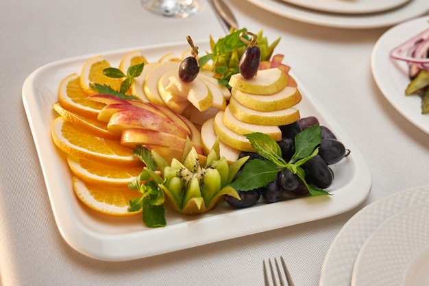 Plate with sliced fruit stands on a served table in a restaurant Premium Photo
