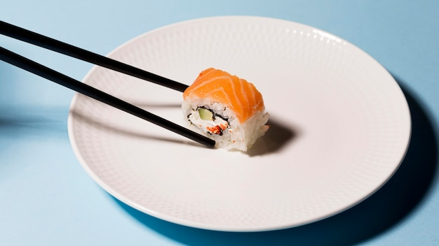 Plate with sushi roll and chopsticks Free Photo
