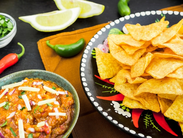 Plate with tacos near cup of garnish and vegetables Free Photo