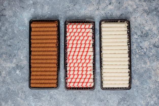 Plate with tasty wafer roll sticks on concrete surface Free Photo