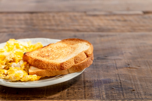 Plate with toast and eggs, on a rustic wooden table. horizontal photo with space for text Premium Photo