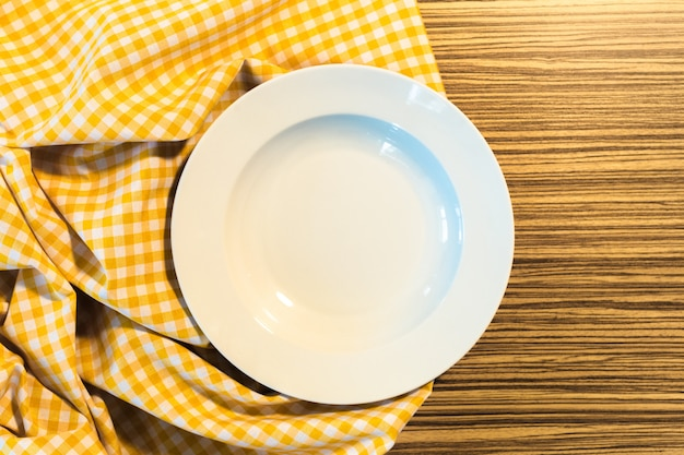 The plate on yellow checkered table cloth Premium Photo
