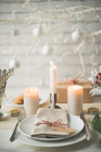 Plates and cutlery set up on table for christmas dinner Free Photo