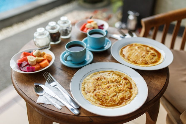 Plates with banana pancakes, tropical fruits and two cups of coffee on wooden table. Premium Photo