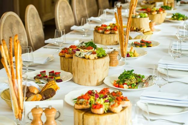 Тарелки с холодными закусками и нарезанным сыром на сервировочном столе Premium Фотографии