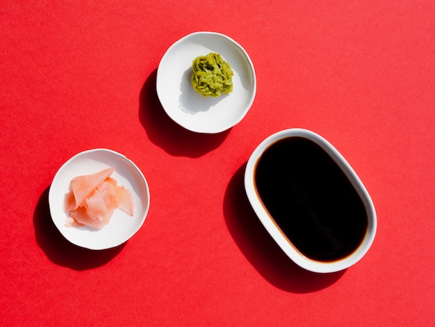 Plates with wasabi and soy sauce on a red backgrund Free Photo