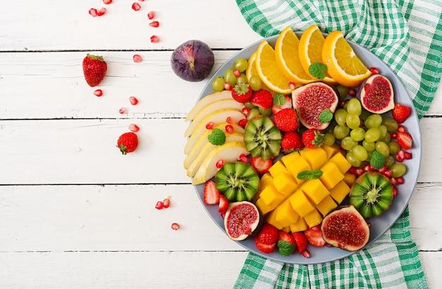 Platter fruits and berries. mango, kiwi, fig, strawberry, grapes, pear and orange. Premium Photo