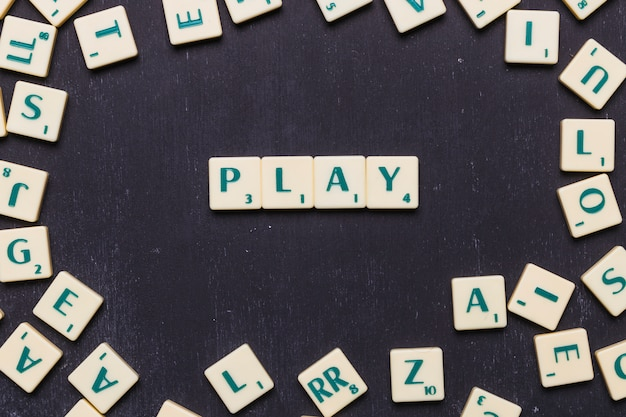 Play scrabble letters over black background Free Photo
