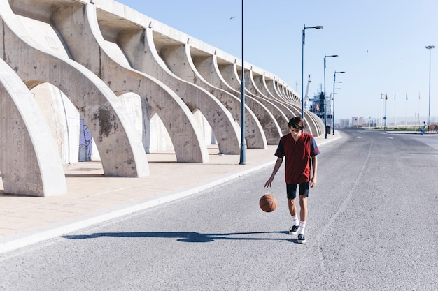 Player practicing basketball on road in city Free Photo
