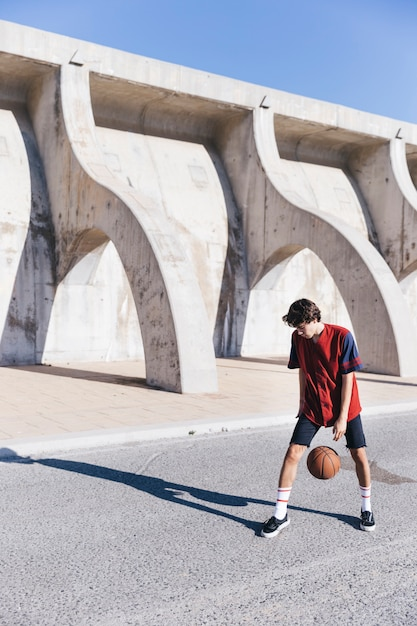 Player practicing basketball on street Free Photo