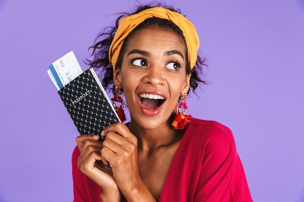 보라색 벽 너머로 멀리 보면서 티켓으로 여권을 들고 드레스에 쾌활한 아프리카 여자 프리미엄 사진