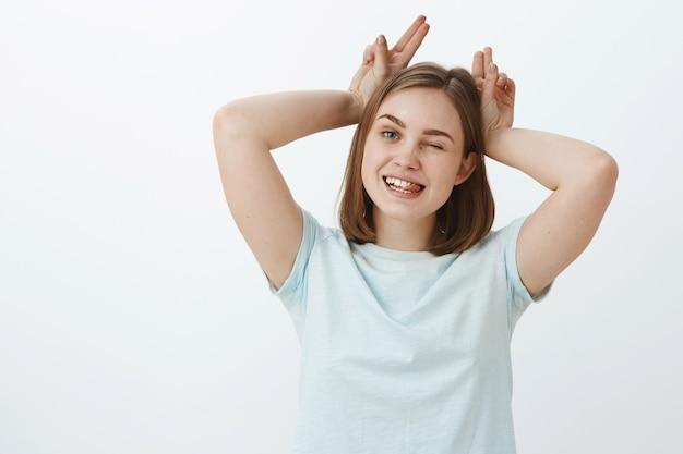 Игривая и веселая беззаботная молодая женщина наслаждается жизнью, проводя время с младшей сестрой, играя, показывая корову или животное с рогами, счастливо подмигивая, высунув язык и держа пальцы на голове Бесплатные Фотографии